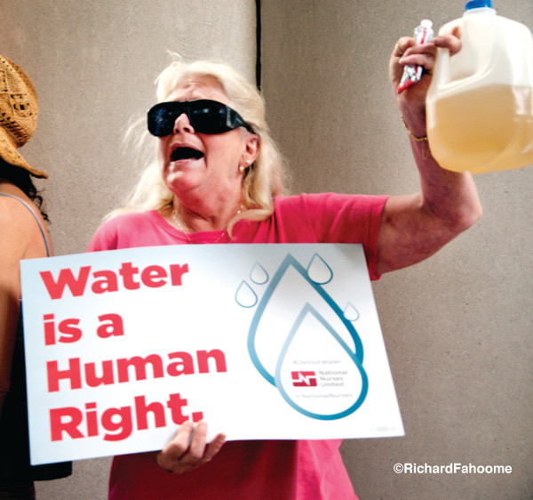 A Flint, MI resident holds up toxic water at a community meeting. The fight for quality water in Flint has reached a critical mass with the discovery of lead in many residents' water (based on a Virginia Tech research study). PHOTO/RICHARD FAHOOME
