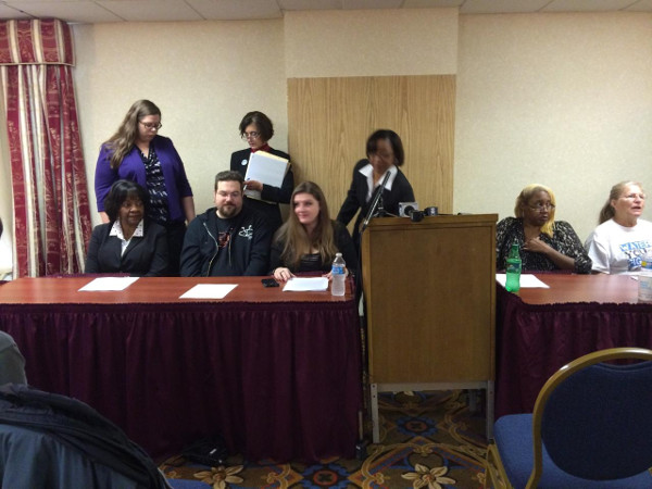 Melissa Mays (left of podium), of the group Water You Fighting For, prepares for a press conference on a class action lawsuit. Flint, MI residents have been subject to E. coli, TTHM's, and now lead poisoning from their water. PHOTO/DONATED