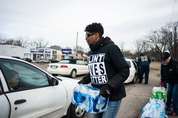 Tonya Kirkland, resident of Flint for 41 years and member of Worker's United Local 2402/2403, hands out water to fellow residents. PHOTO/ADRIAN GARCIA