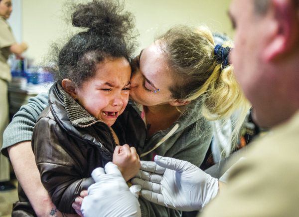 Miracle Martin, 3, cries out as her mother Dawnell Martin, both of Flint, gives her a kiss to calm her nerves during a free lead testing event on Monday, Feb. 8, 2016 at Carriage Town Ministries in Flint. Molina Healthcare provided children up to six years of age with free lead testing, as well as water filters for families to take home and install. Jake May | MLive.com