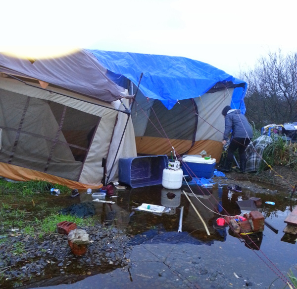 A makeshift tent in a cold, wet, marsh in Eureka, CA where up to 200 homeless people lived before their encampment was destroyed by police in May. PHOTO/KATHY SRABIAN