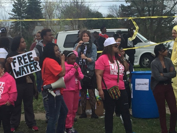"Flint rally where residents urge President Obama, on his recent visit, to resolve the Flint water crisis. The sign on the trashcan says ""Legionaires,"" which is a disease residents have died from after the water contamination. On the right, a man wears a hazmat suit.  Photo/Paul Spectacle Productions"