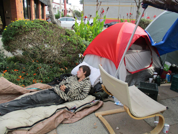"Dimitri rests from his overnight security shift at the Poor Tour. ""First They Came For The Homeless"" tent community in Berkeley CA. PHOTO/SARAH MENEFEE"